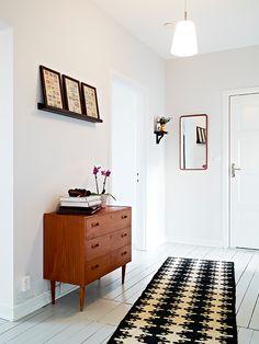 Cômoda em madeira, quadrinhos apoiados em prateleira e tapete com estampa gráfica