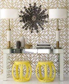 Papel de parede com grafismo dourado, combina com a estrutura das luminárias e o aparador de espelho praticamente some na composição